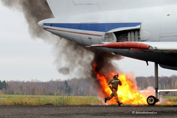 Пожарный на фоне горящего самолета в аэропорту