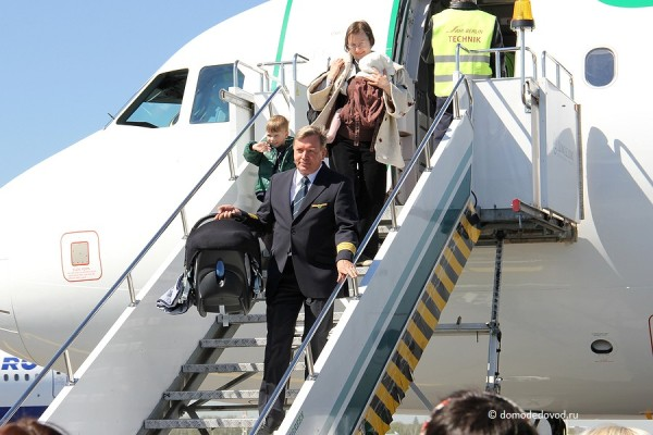 Пилот помогает пассажирам спуститься по трапу.