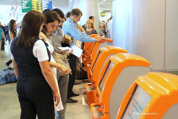 Консультант помогает пассажирам зарегистрирваться на рейс