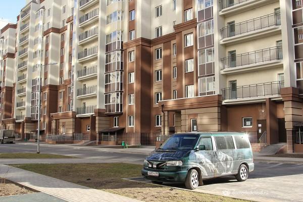 Застекленные балконы отбрасывают солнечные зайчики на соседние дома